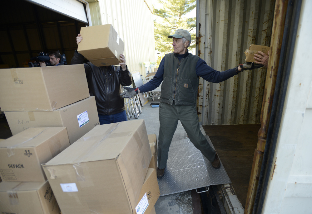John Nolan passes a box into a truck as Partners for World Health prepare to ship out over 900 boxes of needed medical supplies to Syria on Monday. The South Portland nonprofit began in Elizabeth McLellan's home in 2007.