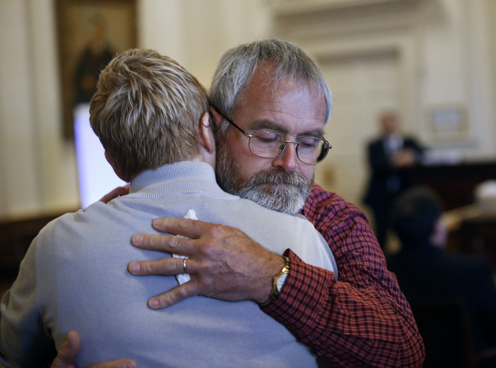 Jeffrey Boudreau, the husband of Wendy Boudreau, embraces one of his daughters after they testified in November 2015 at the sentencing hearing in Alfred for Connor MacCalister, who pleaded guilty to murdering Wendy Boudreau.