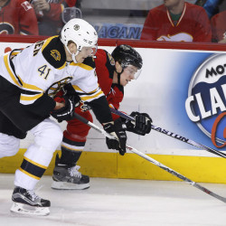 Boston's Joonas Kemppainen, left, gets his stick in front of Calgary's Mason Raymond during the first period of a 5-4 Bruins loss in overtime at Boston.