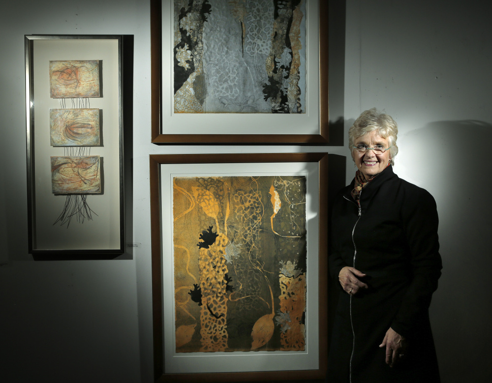 "Kate Chappell at her Westbrook studio with recent works. The two at center are collagraph monoprints titled ""Earth Matrix I"" (bottom) and ""Earth Matrix II."" At left is a mixed-media piece called ""Flute of Interior Time."""