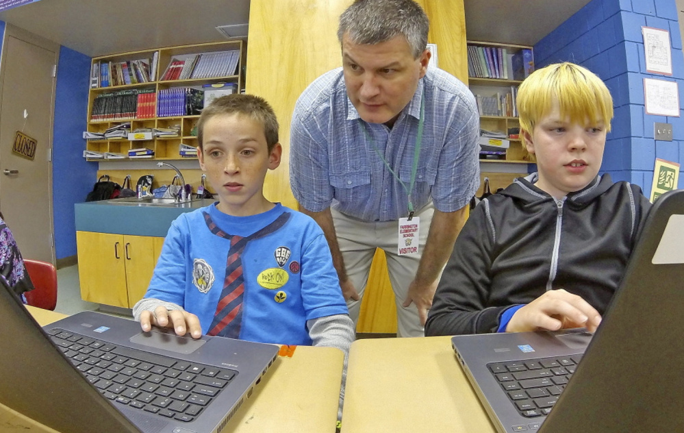 Kepware Technologies CEO Tony Paine, shown overseeing Augusta's Farrington Elementary School fourth-graders Gabriel Biasuz, left, and Jared Barker, who are using laptops that his company donated, says the impending sale won't affect Kepware's local footprint.