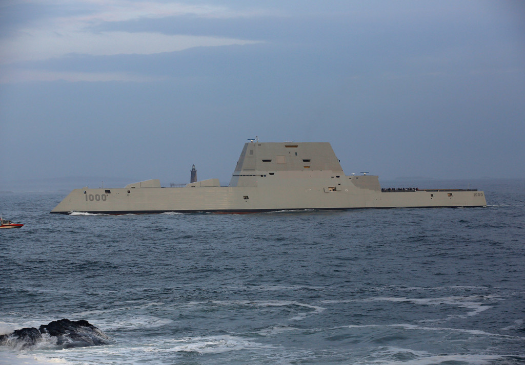 The Zumwalt-class destroyer passes Fort Williams State Park, with Ram Island Ledge Lighthouse in the background, on its way into Portland Harbor on Thursday.