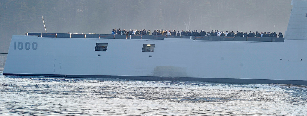 Hundreds of VIPs onboard watch the shoreline as The Zumwalt launches from Bath Iron Works in Bath.