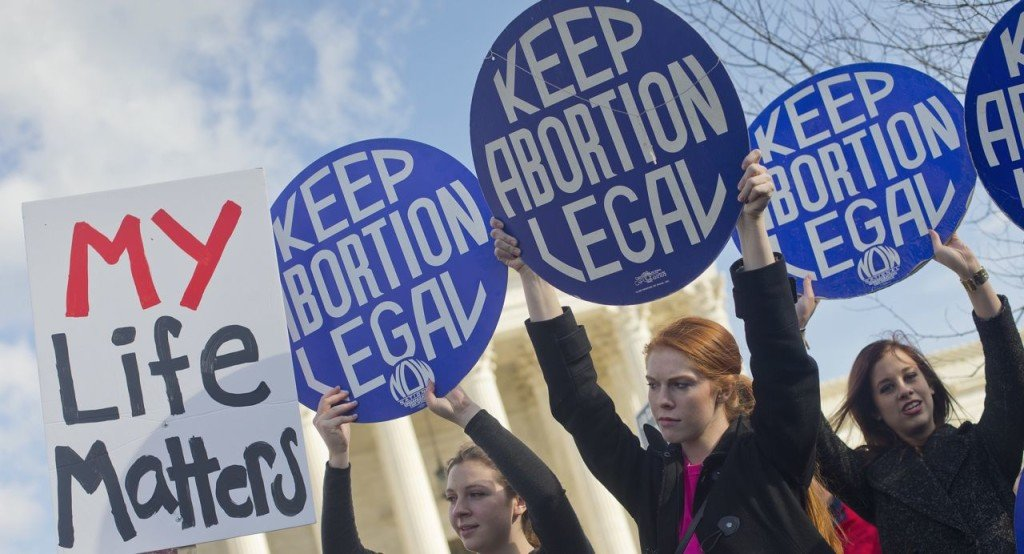 Pro-abortion rights supporters hold up signs in front of the Supreme Court on Jan. 22, 2015, the same day thousands of anti-abortion demonstrators took part in  the annual March for Life to protest the Supreme Court's landmark 1973 decision that declared a constitutional right to abortion. The Associated Press