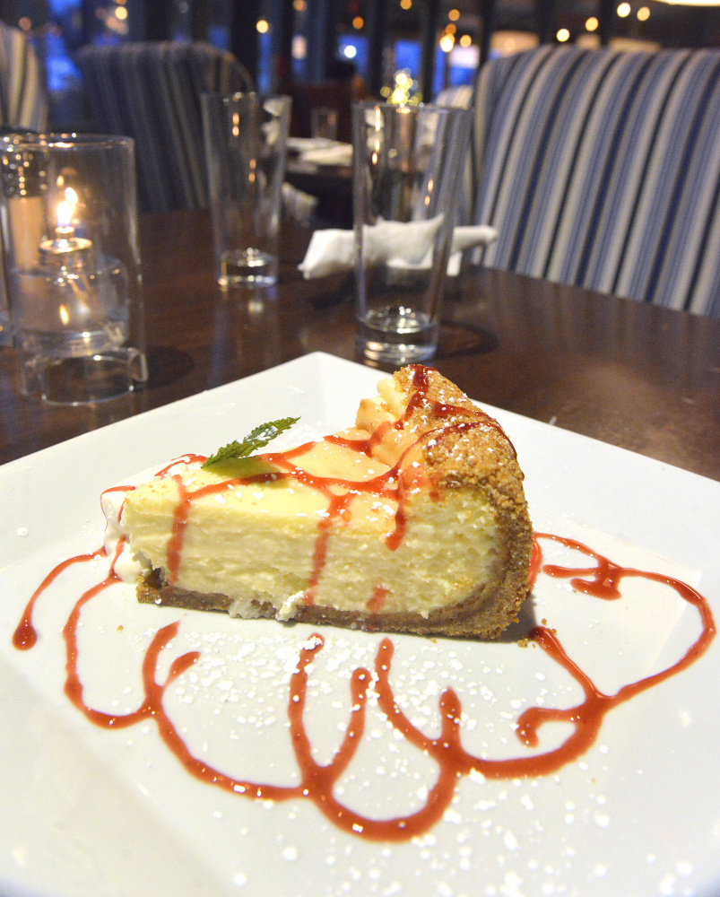 New York-style cheesecake with graham cracker crust and raspberry coulis.