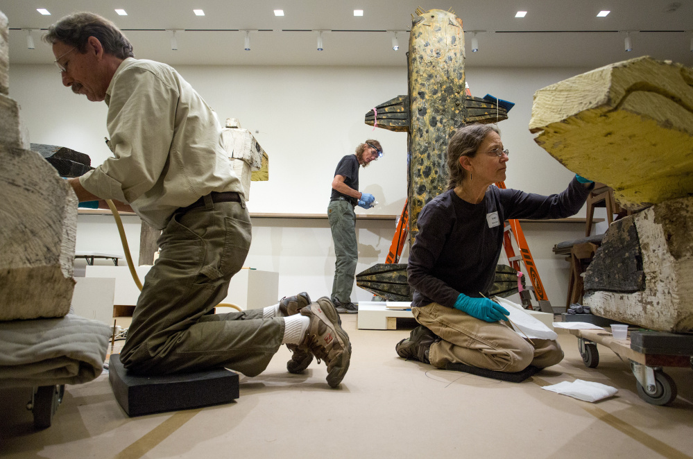 Ron Harvey, left, Michael Hudak and Nancy Bixler restore sculpture by Bernard Langlais at the Portland Museum of Art. Artwork by Langlais and other Maine artists will be displayed in the new fourth-floor Modern Menagerie gallery after the museum reopens on Jan. 22.