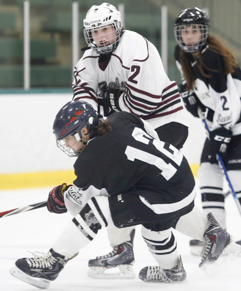 Maura Verrill of Greely watches after firing a shot as she is being checked by Katya Fons of St. Dominic during the second period.