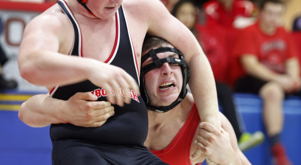 Aren Dickman, left, of Scarborough and Mike Hurst of Sanford grapple during their 195-pound match. Hurst finished fourth in the division, which Dickman placed sixth.