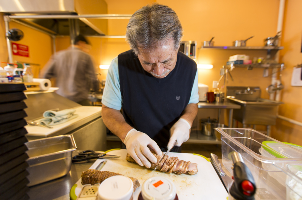 Kei Suzuki, owner of Ramen Suzikaya, slices roasted pork in preparation for the lunch rush while chef Peter Smith, in background, steams vegetables.