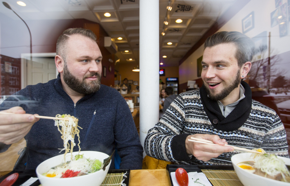 Saco residents Kyle Holmquist, left, and Bradley De Rosa dig into bowls of ramen from their window seats at Ramen Suzikaya on Congress Street in Portland.