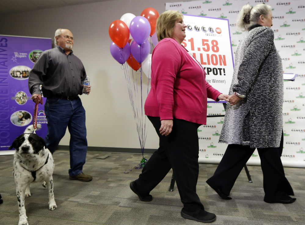 John Robinson brings in the family dog, Abby, as Robinson's wife, Lisa, center, arrives for a news conference with Rebecca Hargrove, president and CEO of the Tennessee Lottery, on Friday in Nashville, Tenn.