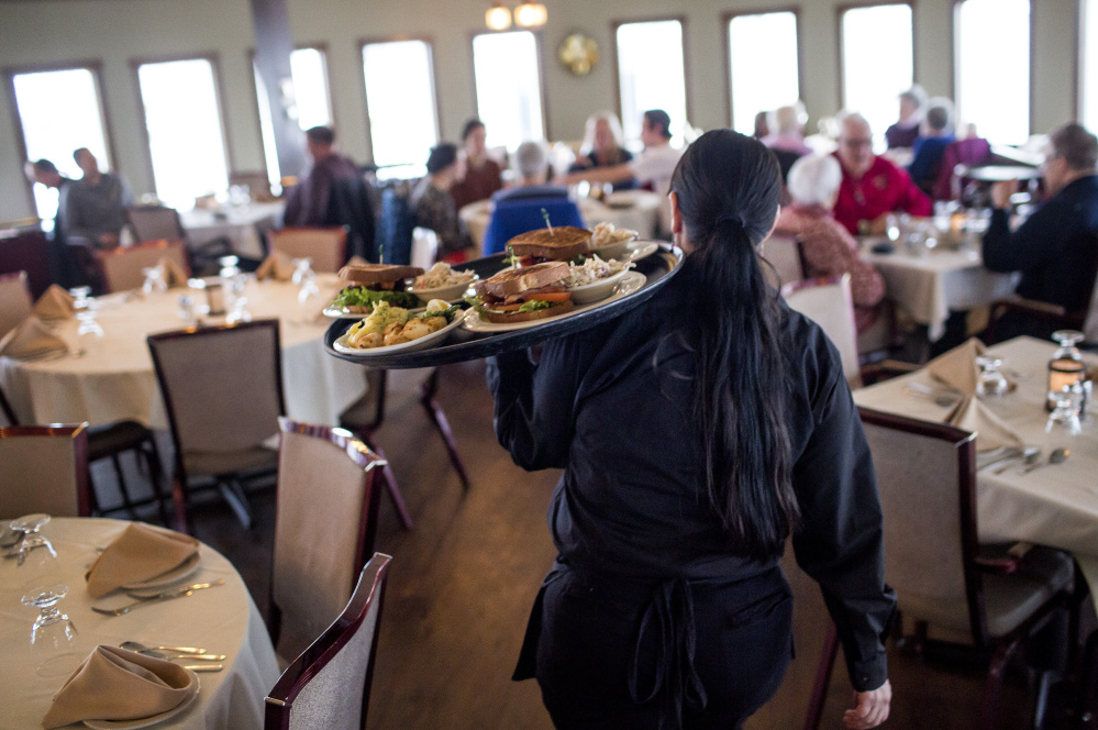 """Dawn Murray, a server at DiMillo's On the Water, carries food to waiting customers during the lunch rush Friday at the Portland restaurant. Her employer, Steve DiMillo, says, """"It's time for someone to make a call (about the legality of Portland's wage ordinance), so they don't leave operators or the wait staff not knowing what their pay should be."""""""