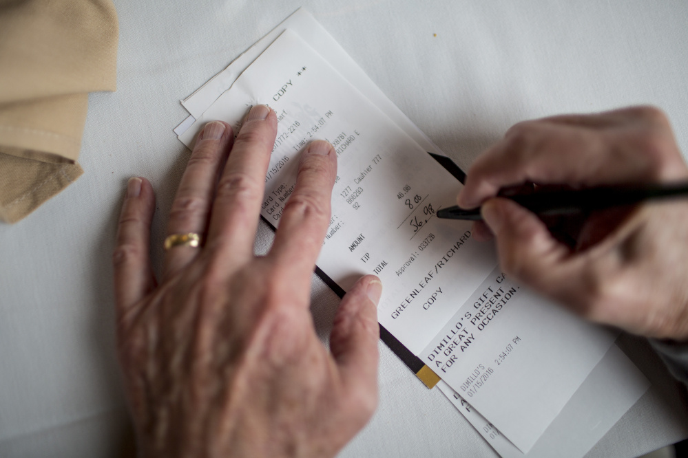Richard Greenleaf of Gorham fills in the tip amount on a check after eating lunch with friends at DiMillo's On the Water Friday. Gabe Souza/Staff Photographer