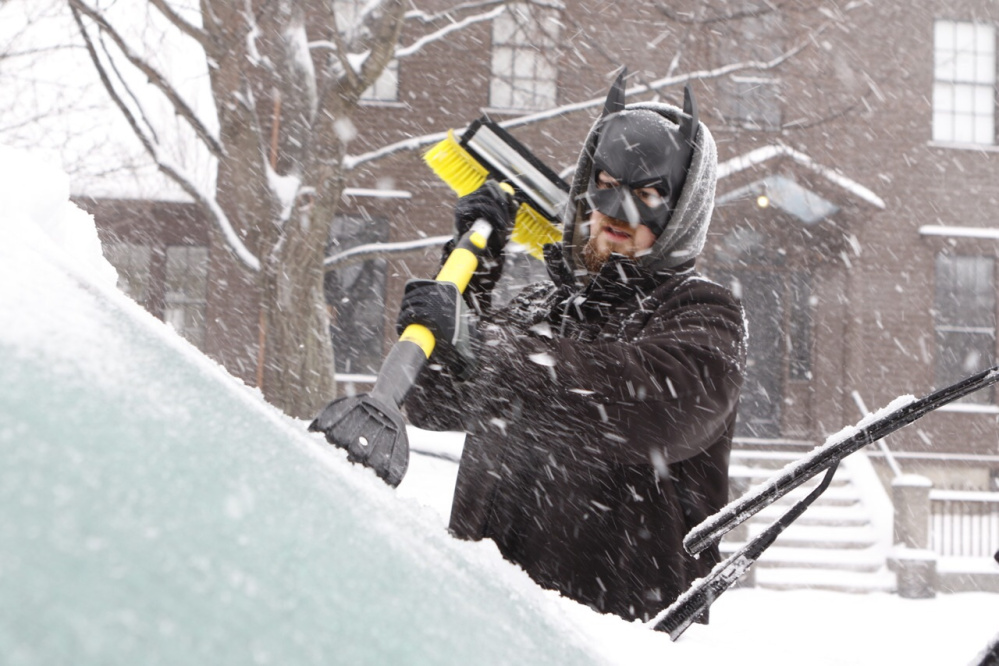 Spencer Holmes wears a Batman mask as he scrapes his windshield on Saturday in Portland.