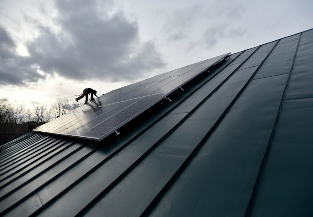 Jake Hunt, with Insource Renewables, installs solar panels Tuesday on the roof of the Vassalboro Friends Meeting building in Vassalboro – a project the group hopes will inspire other organizations to reduce use of fossil fuels. Morning Sentinel photo