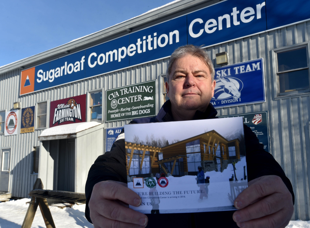 Bruce Miles, president of the Sugarloaf Ski Club, holds a rendering of a proposed Competition Center while standing in front of the existing competition center.