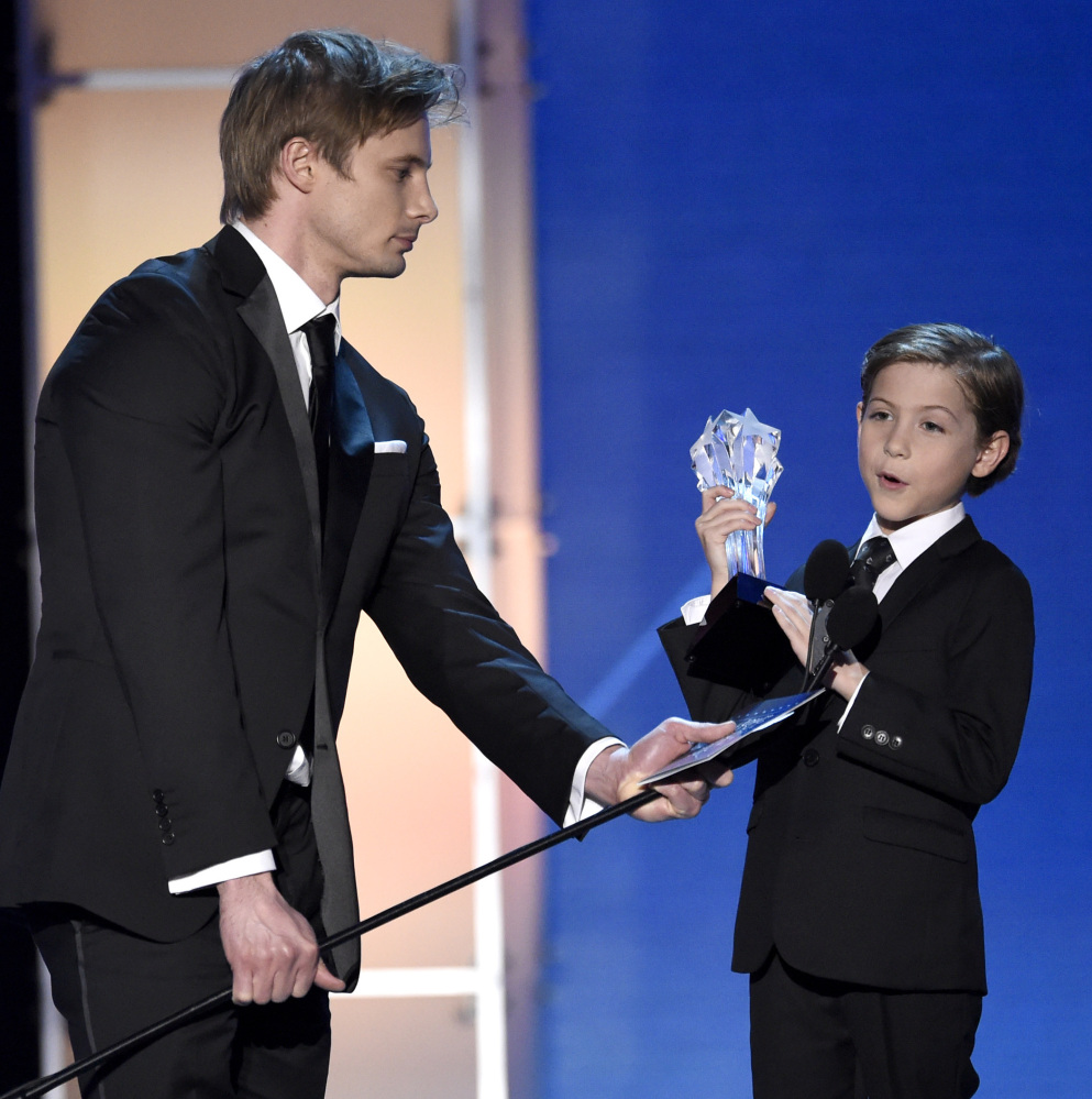 """Bradley James, left, holds the microphone for Jacob Tremblay as he accepts the Critics' Choice Award for best young actor/actress for """"Room."""""""