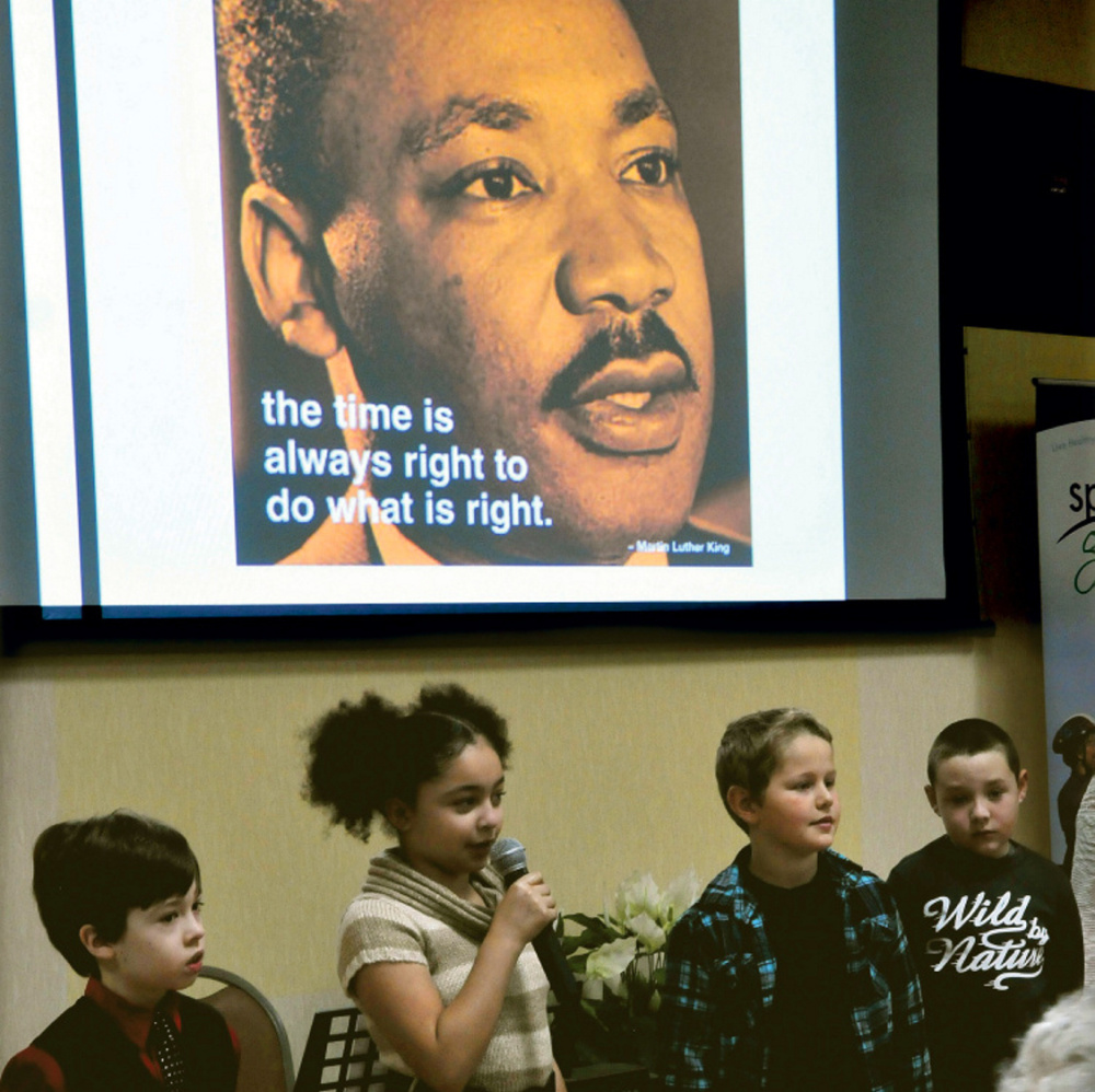 Students from George Mitchell School, including Isabella Bohner, center, recite passages Monday during the Martin Luther King Jr. breakfast celebration at the Muskie Center in Waterville.