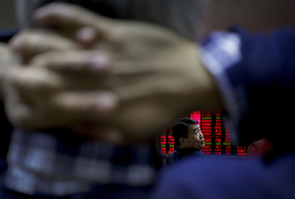 A man chats with other investors near an electronic board displaying stock prices at a brokerage house in Beijing, Tuesday.