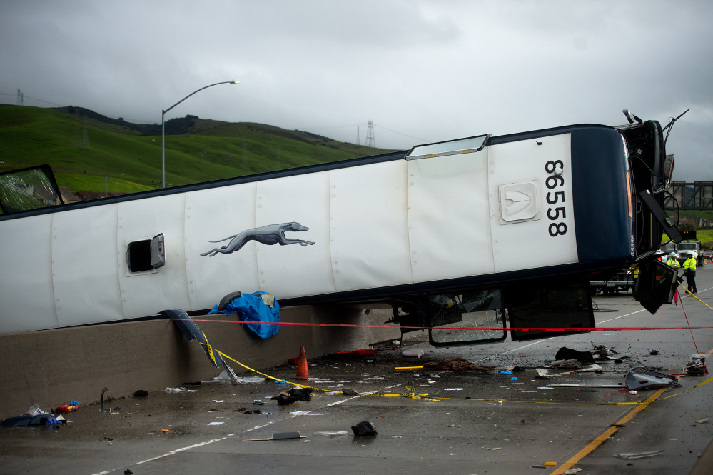 A Greyhound bus that lost traction and became airborne sits atop a concrete highway divider on Tuesday in San Jose, Calif.