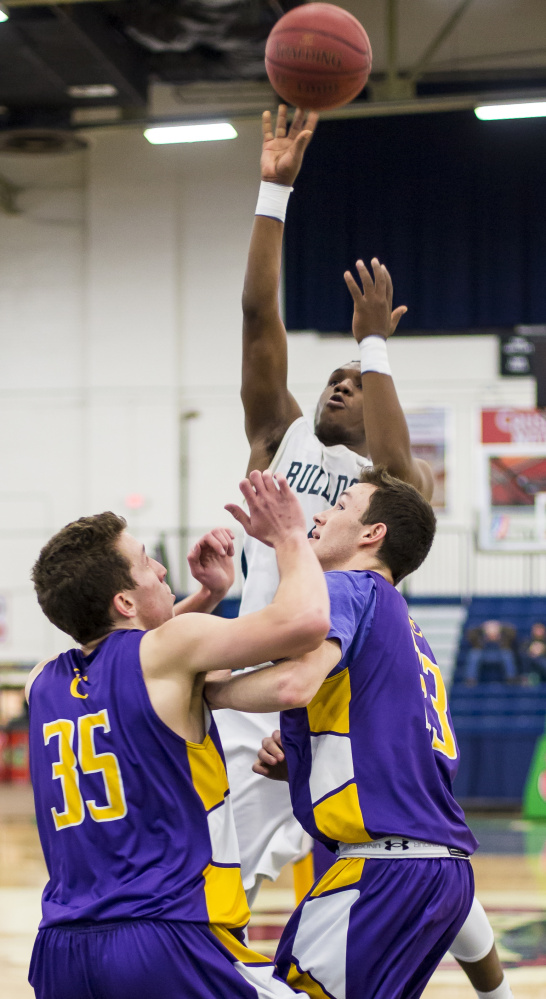Amir Moss, who scored a game-high 18 points for Portland, soars for a jump shot over the Cheverus defense. The Bulldogs, executing their offense well, hit 68 percent of their shots in the deciding first half.