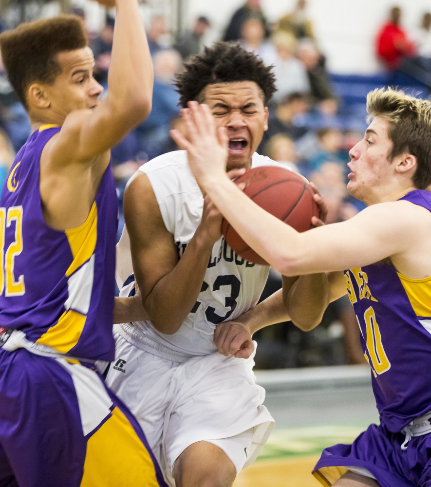 Portland freshman Trey Bellew tries to break through to the basket between Tre Fletcher, left, and Jake Tomkinson of Cheverus during Portland's 72-42 victory Wednesday night at the Portland Exposition Building.