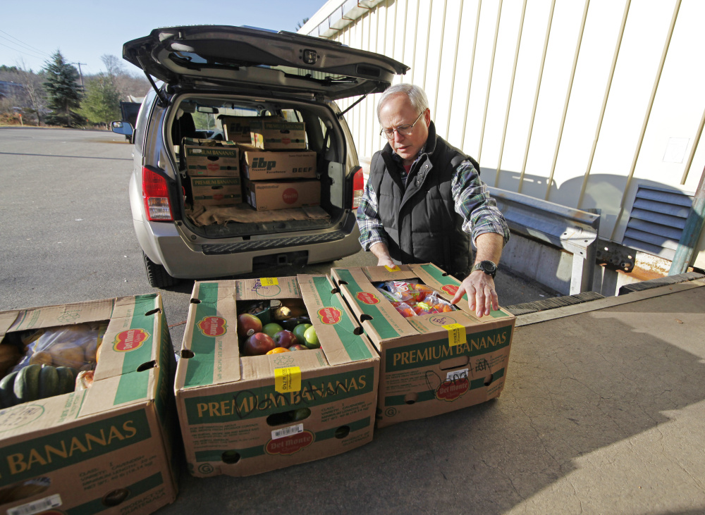 Volunteer Doug Horner loads boxes of day-old produce from Hannaford in Westbrook into his vehicle to take to the Stroudwater Food Pantry in Westbrook. Jill Brady/Staff Photographer