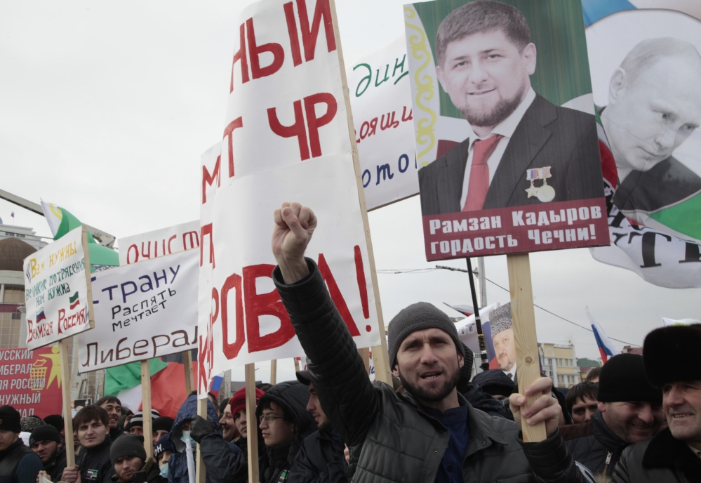 Chechen demonstrators hold portraits of Russian President Vladimir Putin and Chechen regional leader Ramzan Kadyrov as they listen to an orator during a massive rally in Grozny, Russia, on Friday.