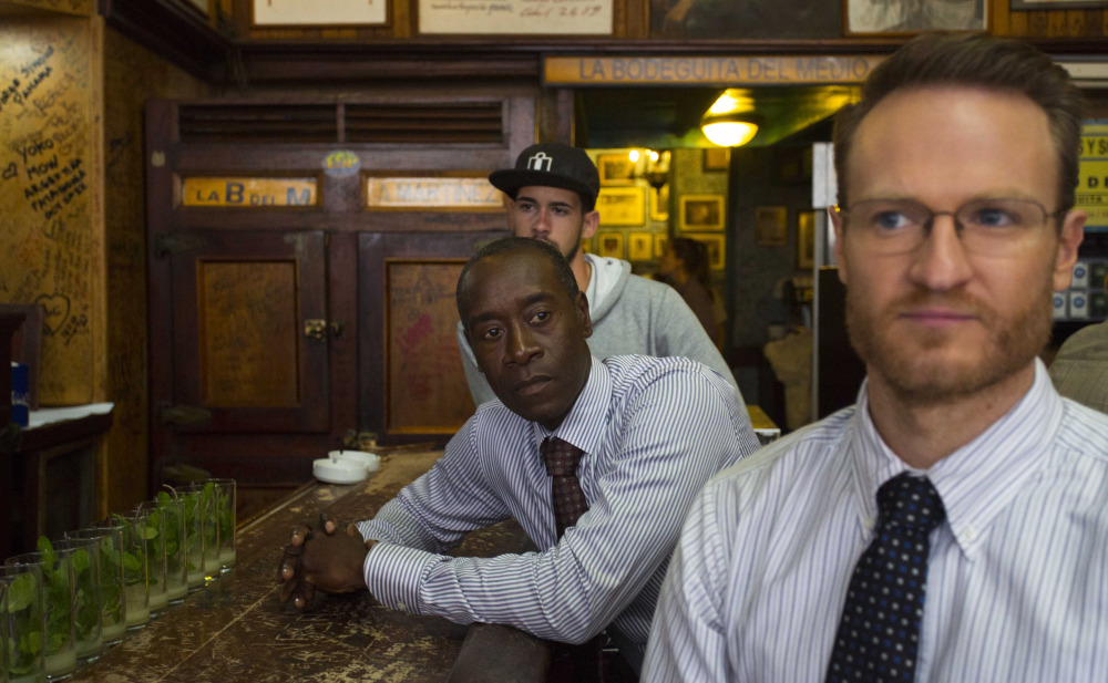 """""""House of Lies"""" actors Don Cheadle and Josh Lawson, right, sit at a counter in Bodeguita Del Medio during the filming of an episode in Havana, Cuba. The producers of Showtime's dark comedy wanted to shoot the first episode of scripted American television in Cuba in more than half a century."""