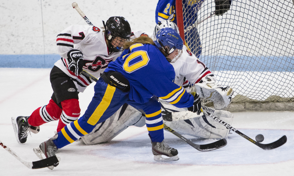 Falmouth's Devon Sarazin shoots the puck past Scarborough goalie McKenzie Cormier for the first of her two goals Friday as Grace Murphy tries to defend Friday at MHG Ice Centre. Unbeaten Scarborough rallied for a 3-2 win in overtime.