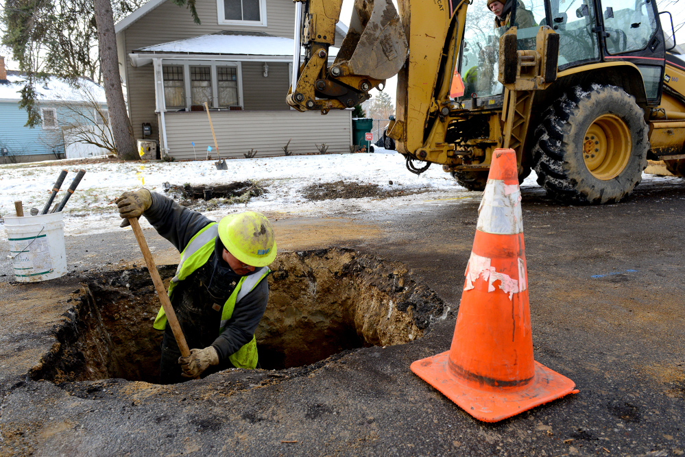 Richard Garza moves dirt around the water main after replacing the lead water pipe with a new copper one Friday at a home in Lansing, Mich.