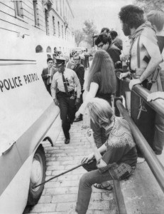 Brad Fox, 20, tries to deflate a tire on a police van outside the Cannon House Office Building in Washington, D.C., on Oct. 6, 1968. Inside the van were anti-war activists Abbie Hoffman and his wife, Anita, who had been arrested because Hoffman was wearing a shirt that looked like the U.S. flag. Hoffman, who was the leader of the anti-establishment Youth International Party or Yippies, was there to testify before the House Un-American Activities Committee about clashes that had occurred between police and protesters at the 1968 Democratic National Convention in Chicago. Fox, who was a Yippie organizer, also was arrested and jailed overnight. To his right is Jerry Rubin, another Yippie leader, with no shirt or shoes and a toy AK-47 slung from his shoulder.