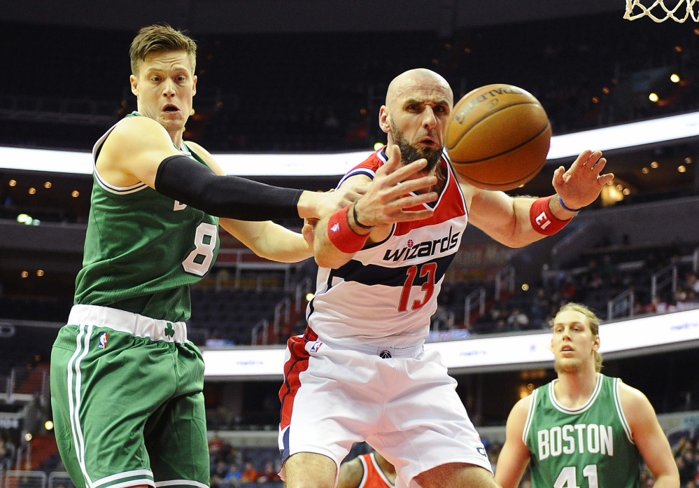 Wizards center Marcin Gortat reaches for the ball as Celtics forward Jonas Jerebko looks on in the first half of Monday night's game.
