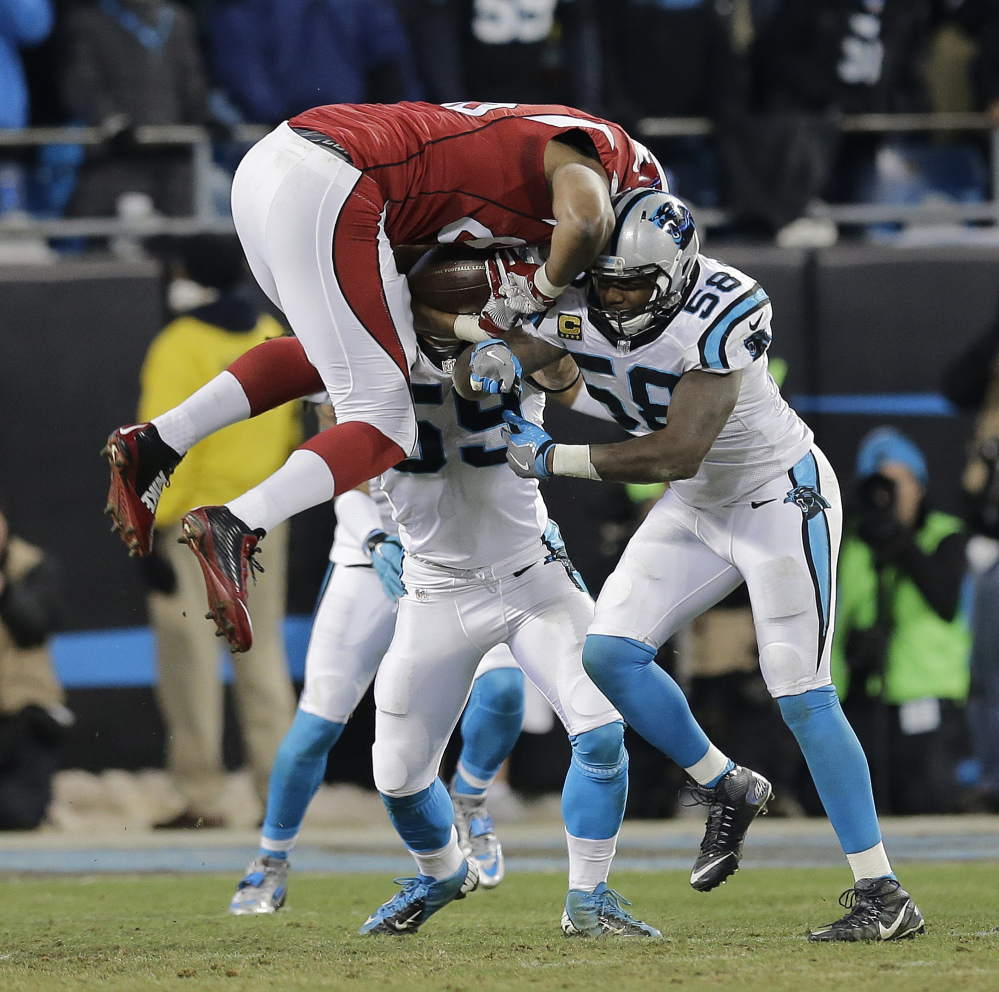Arizona Cardinals' Darren Fells is hit by Carolina Panthers' Thomas Davis (58) and Luke Kuechly after catching a pass during the first half the NFL football NFC championship game Sunday in Charlotte, N.C.