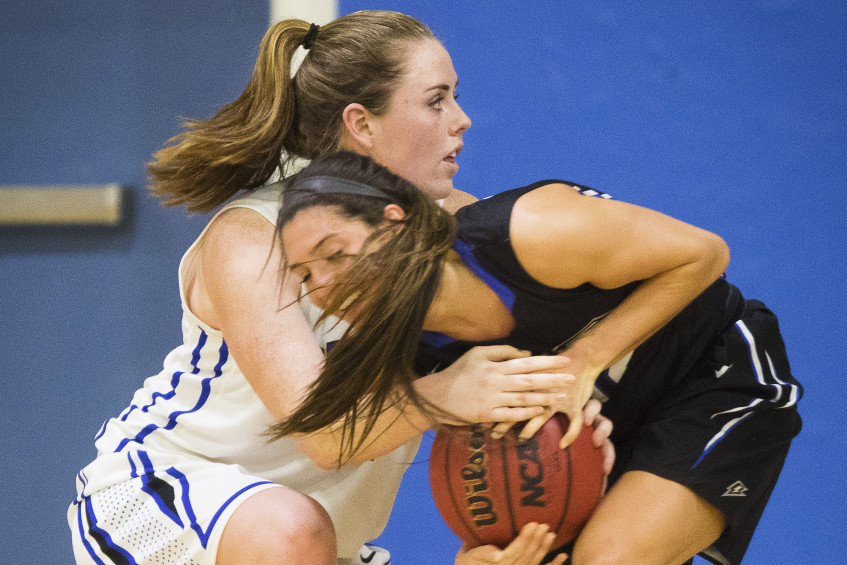 Morgan Cahill, left, of St. Joseph's battles UNE's Sadie DiPierro during a 78-55 win by the Nor'easters at Standish on Monday. DiPierro, a McAuley graduate, led UNE with 17 points and nine rebounds