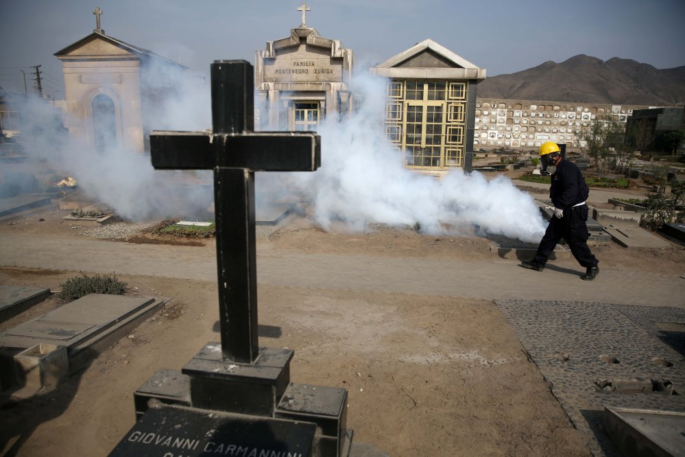 A health worker fumigates to prevent Dengue, Chikunguya and Zika virus, at a cemetery in Lima, Peru.