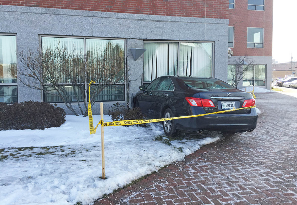 Part of the AAA of Northern New England building on Marginal Way was evacuated Tuesday morning until a structural engineer could determine whether it was safe to remove the car that crashed into the structure.