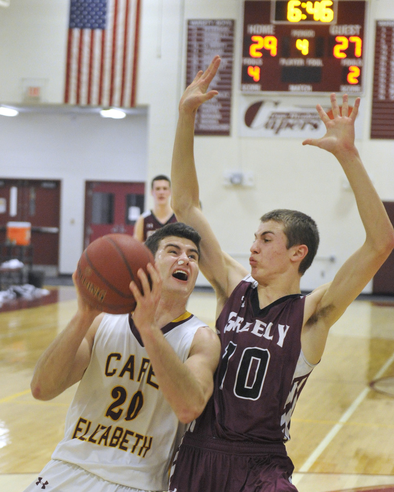 Cape Elizabeth's Justin Guerette, left, drives to the basket against Greely's Ryan Twitchell during the Capers' 45-38 win Monday in Cape Elizabeth.