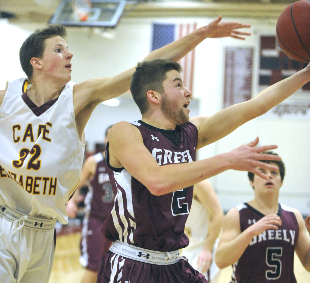 John Ewing/Staff Photographer Greely's Caleb Normandeau, right, takes a shot while being defended by Cape Elizabeth's James Bottomley on Monday in Cape Elizabeth.