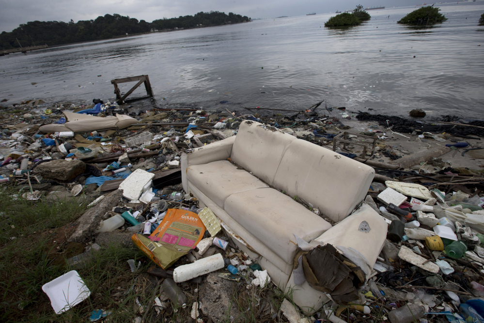 FILE - In this June 1, 2015 file photo, a discarded sofa litters the shore of Guanabara Bay in Rio de Janeiro, Brazil. About 1,600 athletes will compete in Rio during the 2016 Summer Olympics. Hundreds more will be involved during the subsequent Paralympics. Experts say athletes will be competing in the viral equivalent of raw sewage with exposure to dangerous health risks almost certain. Many sailors have described the conditions as