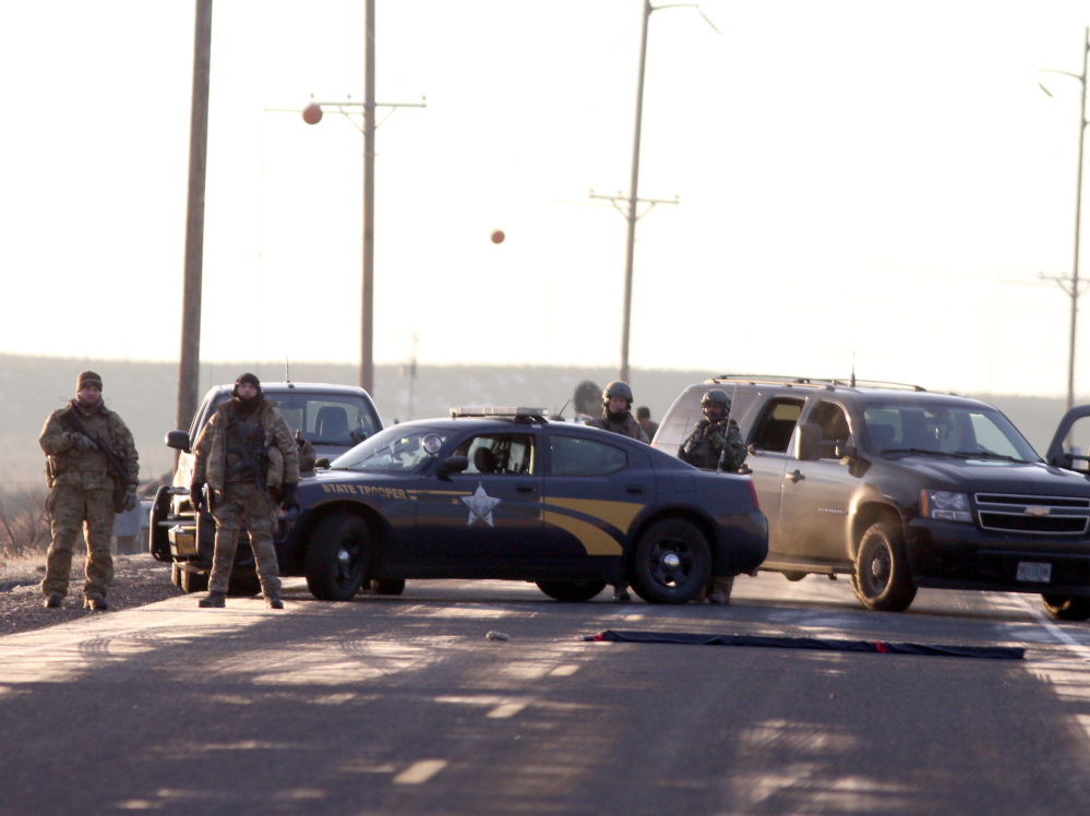 Beth Nakamura/The Oregonian via AP Above: Authorities restrict access Wednesday to the Oregon refuge being occupied by an armed group after one of the occupiers was killed during a traffic stop and eight more, including the group's leader, were arrested.