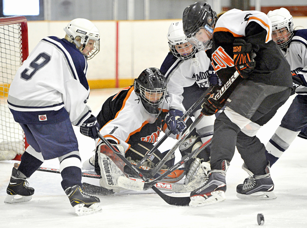 The puck squirts away from Winslow/Erskine goalie Kiana Richards as teammate Bailey Robbins fights for the rebound with Madi McCallum, left, Keeley Arnold, center, and Colleen Sullivan of Yarmouth/Freeport/Gray-New Gloucester during a girls' hockey game Saturday.