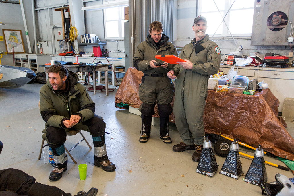 Lee Kanter, far right, a state moose biologist, has a laugh as he plans a flight with members of Native Range Capture Services at the Department of Inland Fisheries and Wildlife's Greenville office. Kanter was working with Native Range, a Nevada-based company, to capture moose, place GPS-enabled collars on the animals, and collect blood, hair and feces specimens, before releasing them back into the wild.