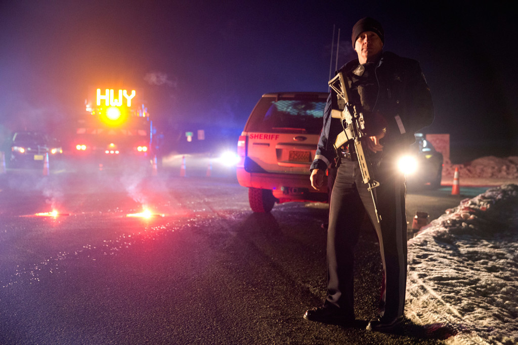 Sgt. Tom Hutchison stands in front of an Oregon State Police roadblock on Highway 395 on Tuesday night between John Day and Burns, Ore. The FBI arrested the leaders of an armed group that has occupied a federal wildlife refuge in eastern Oregon for the past three weeks. Dave Killen/The Oregonian via AP