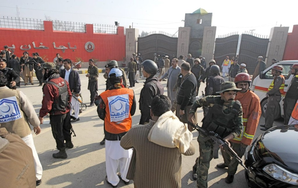 Troops and rescue workers gather at the main gate of Bacha Khan University in Charsadda town, 21 miles outside the city of Peshawar, Pakistan, Wednesday. Gunmen stormed the university, which is named after the founder of an anti-Taliban political party. The Associated Press