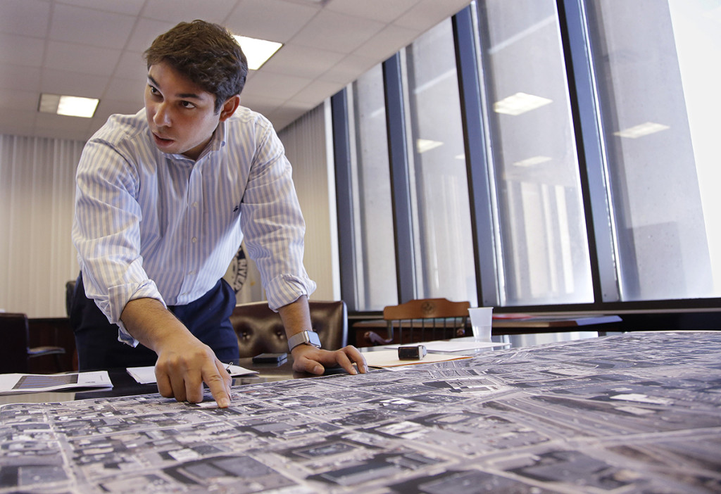 Newly elected Fall River Mayor Jasiel Correia reviews grid maps of the city's downtown at his city hall office in Fall River, Mass. The Associated Press
