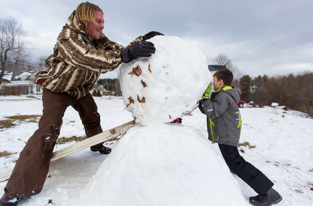 Ryan Bellemare, left, and his son Blake, 5, use a ramp to roll the middle section of a snowman into place Sunday in Auburn. The snowball, which weighed an estimated 250 pounds, broke another wooden ramp just minutes earlier. A winter storm on Friday blanketed southern Maine with wet snow -- ideal for making snowballs and snowmen.