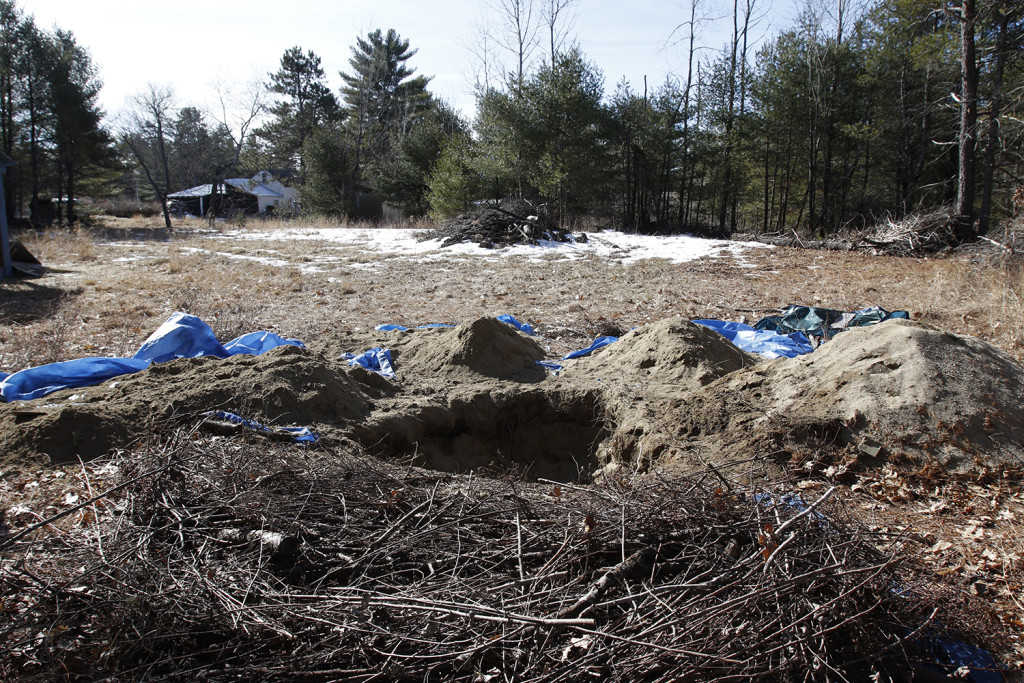 A hole is seen behind the home of Shawn Farnell Tuesday in Baldwin, Maine. Joel Page/Staff Photographer
