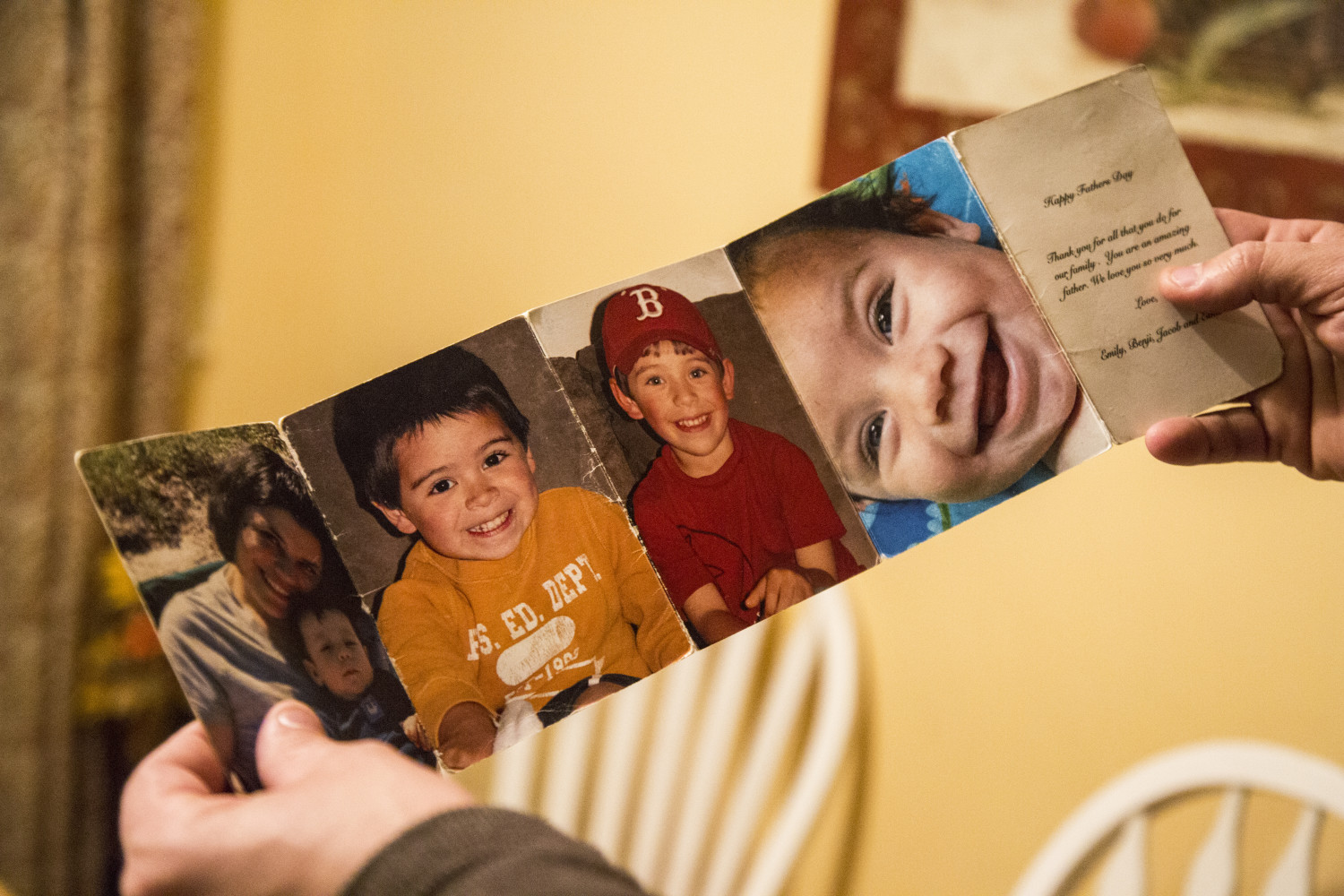 Mark Tidd holds up one of his favorite Father's Day gifts, a folded display of photos of his children, including his daughter Lucy Tidd, in the red baseball cap, in Portland.
