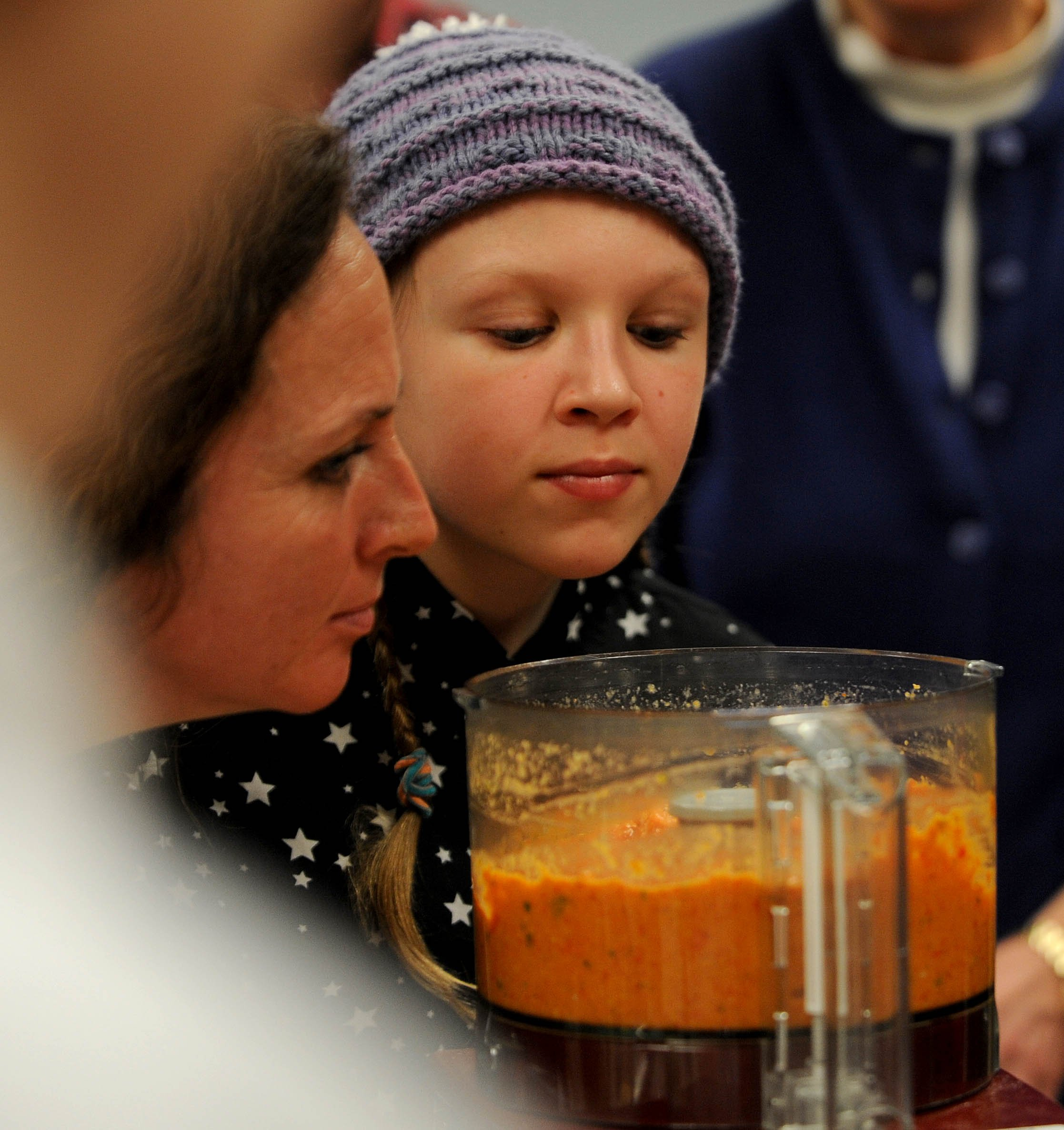 Kate Kemper, 13, of Unity, leans to smell the freshly made romesco sauce to go with the venison polpettina. Michael G. Seamans/Kennebec Journal